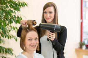 hairdresser making locks with barrel brush and blow-dryer